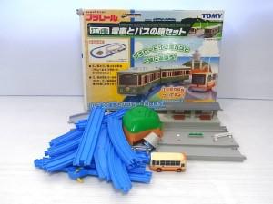 プラレール 江ノ電 電車とバスの旅セットの外箱と中身。奥に箱が有り、手前には青いレールや緑のトンネル、電車などが置かれている。