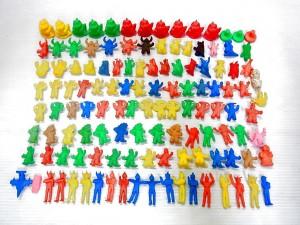白い背景に、赤、緑、青と色とりどりの、円谷プロ ウルトラマンの消しゴムが並んでいる。奥には怪獣のキャラクターもいる。それぞれポーズを取っている。