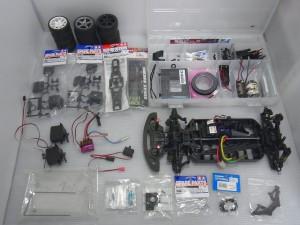 白で統一された空間に積まれたタイヤや、シャーシ、タミヤのラジコン用のパーツなどが置かれている。透明のビニールに入った物や、クリアケースに入ったモーターなども有る。