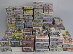 SD戦国伝 ガンダム BB戦士のプラモデルの箱が大量に積み上げられている。ガンダムのイラスト入りの表紙や側面が見える。