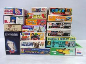 様々なプラモデルの箱が積まれている。アニメのイラストや商品名が書かれている。