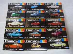 トミカ黒箱が並んでいる。全体的に黒色で、正面には車のイラストが書かれている。その他にロゴや商品ナンバーが書かれている。