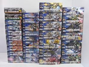 バンダイ 1/144 HG ガンダムのプラモデルの外箱がたくさん積まれている。各イラストや商品名が書かれている。