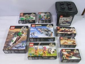 箱付きのレゴが並んでいる。パッケージには組立後のイラストや、ロゴマークが書かれている。黒いバケツも見える。