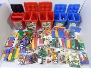 カラフルなレゴが並んでいる。赤や青のバケツや、沢山のLEGOブロックやフィグがある。