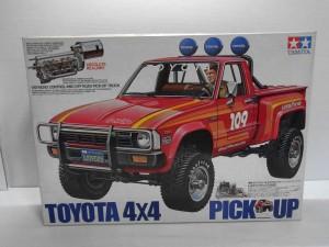 TAMIYA 1/10 トヨタ ハイラックス 4WDの箱。赤い車体や、ドライバーの運転している姿のイラストが書かれている。