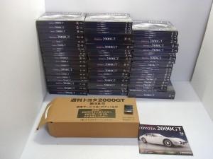 デアゴスティーニ TOYOTA 2000GTの箱が並んでいる。黒い箱に、手前には茶色いダンボール箱も見える。