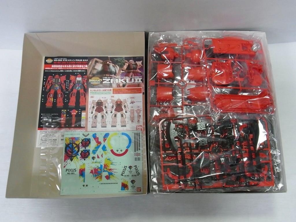 ザク IIのプラモデル展開画像。半分は赤いプラモデルのパーツが収納され、もう半分は説明書やデカールが入っている。