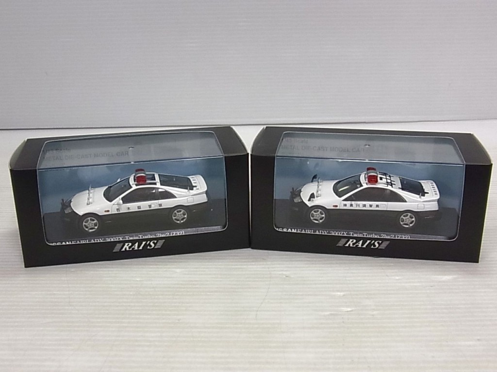 RAI'S レイズのミニカーが2つ並んでいる。両方パトカーで、白と黒のツートンカラー。赤いパトライトも見える。
