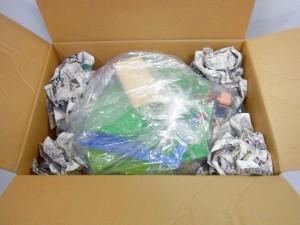 ダンボール箱に、袋に入れられたレゴが入っており、周りに新聞紙が入れられている。