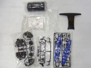 ラジコンの各種パーツ。黒や青のパーツが見える。