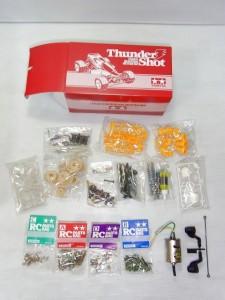 タミヤ Thunder Shot RCの赤い箱の中身。ネジやモーター。黄色のパーツなどが見えている。