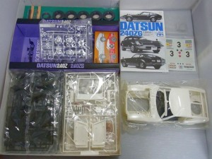 TAMIYA DATSUN 240ZGの展開画像。白いボディや黒いパーツなどが広げられている。