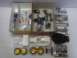 タミヤ 1/10 スーパーファイターGのラジコンの展開画像。黄色いタイヤホイールや白いボディや黒いパーツなどが見える。