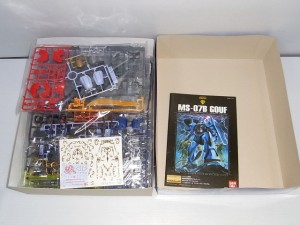グフのプラモデルの青い箱の内容物、金色のエングレーブシール、説明書が載っています。