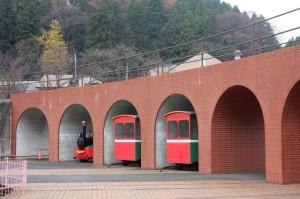 トンネルの画像。茶色いレンガ調で奥には山が見える。中には赤い鉄道も見えている。