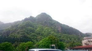 白い空に青々とした山が写っている