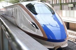 写真いっぱいに白に青ラインの新幹線E7系が写っている