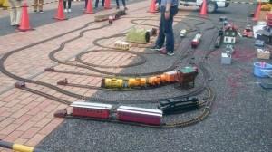 大型鉄道模型がアスファルトの上に並べた線路を走っている
