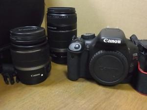 茶色の背景にカメラ本体と交換用レンズが2本写っている