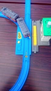 青いポイントれーるに車両が走っている。左にポイント切り替え