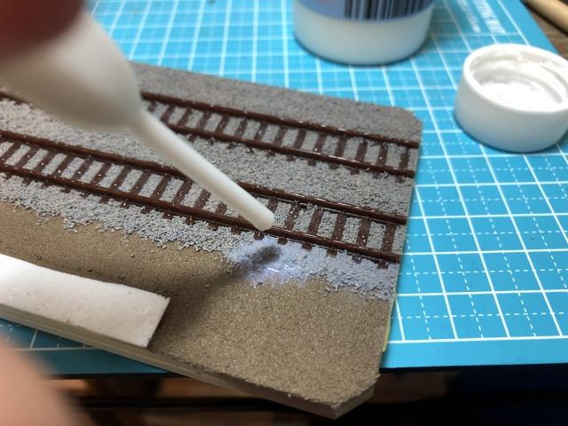 鉄道コレクションに付属している展示用レールにバラストを撒き、固着させる。