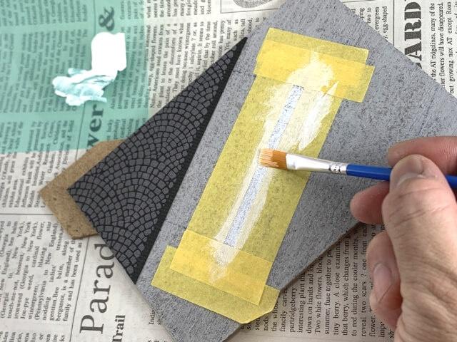 17.マスキングテープの囲いを、白線にしたい部分にかぶせてベースに貼り付け、白絵の具を上からたたくようにして塗る